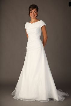 "This modest wedding dress features pleated organza through an asymmetrical dropped waistline along a princess cut gown. A stylish built in cowl wraps around the shoulders and forms a slight ""V"" neckline."