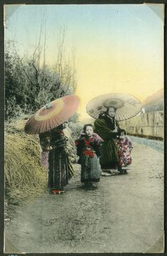 Two women with umbrellas and children in a village, Japan