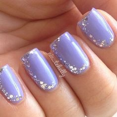 A nail art design in blue matte polish adorned with silver dust on top cut out in various shapes.