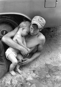 Man and baby on ground leaning against car, Kentucky, 1972, photograph by William Gedney.