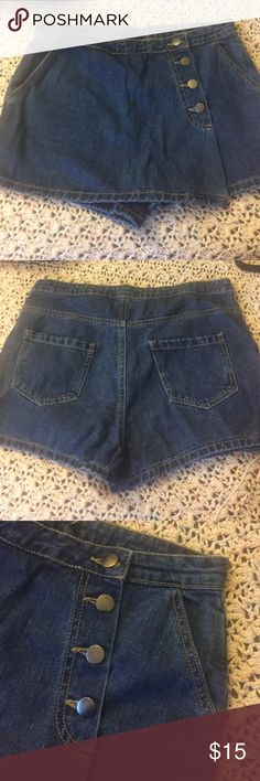 Vintage denim skort Vintage denim skort size medium, medium dark wash with silver hardware, shorts are exposed in the back but looks like a skirt in the front, missing button on top of zipper this is reflected in the price, make an offer! Vintage Skirts