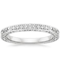 This beautiful antique-style ring is engraved with delicate scrolls that wind around the top and sides of the band. Nine round diamonds adorn the band for eye-catching sparkle. The perfect complement to the Delicate Antique Scroll Engagement Ring (0.10 total carat weight).
