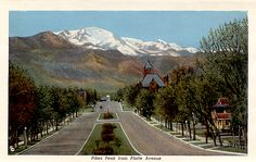 Pikes Peak towers over Platte Avenue in Colorado Springs. Note the large building on the right which was Colorado Springs High School, now Palmer High School. Postcard from about 1930.