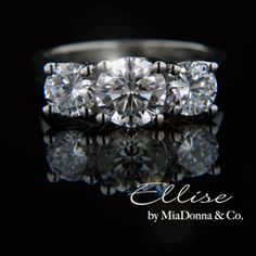 MiaDonna- The Ellise is our most popular Three Stone Engagement Ring. Representing past, present and future this ring is also appropriate as an Anniversary Ring. This outstanding ring is available in a variety of MiaDonna Hybrid Diamond Simulant stone sizes as well as your choice of metal.