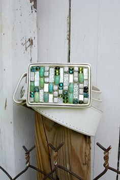 The chunky blocks of aluminum are trade beads hand made from old pots and pans! Very cool way to recycle! Silver glitter glass tiles and silver 24kt gold smalti add some great sparkle. MEMBER - Crooked Moon Mosaics