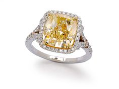 A Coloured Diamond Ring   Set with a cushion-shaped yellow diamond weighing 5.49 carats, to a diamond-set band, mounted in 18k white and yellow gold