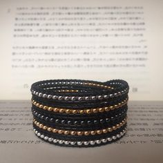 cadeia de 5 voltas de Miyuki rocalla 8/0 em tons de prateado, dourado e antracite em pele preta de 1,5mm. (largura total +/- 3cm)