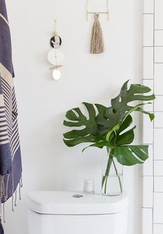 Tropical plant leaves in a vase on the back of a toilet with white subway tile and gray grout, wall hangings and weavings and a striped turkish towel