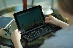 사용자가 '롤리키보드'에 내장된 거치대를 꺼내 태블릿을 올려 놓고 타이핑하는 모습입니다.