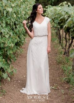Style TR11974 from Mon Cheri Modest is a gorgeous beaded chiffon slim A-line modest wedding gown that has cap sleeves, a soft V-neckline, a blouson bodice, a slightly curved high V-back with a zipper, and a slim chiffon skirt beaded throughout the hips and thighs and scattered down on the lower skirt with a court train. Also great for a beach wedding.