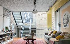 A sala do empresário GG Mattar e da artista plástica Viviana Ximenes acomoda a tubulação do ar condicionado pintada de amarelo, a luminária pendente com várias lâmpadas e teto com isolamento acústico aparente