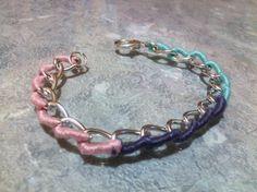 Pulsera de cadena color plata con detalle tejido en colores rosa, morado, y verde.