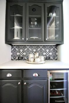 Black butler's pantry features glass-front upper cabinets and black raised panel lower cabinets fitted with a glass door beverage fridge paired with a white countertop and a black and white mosaic tile backsplash, Merola Tile Twenties Classic Ceramic Floor and Wall Tile.