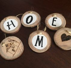 """Wood Slice HOME Garland -  This rustic garland of wood slices and twine is approximately 22"""" long with plenty of extended twine for hanging.  Wood slices are hand painted and embellished with wood burning techniques. Wood slices are adjustable to fit the space you need them for.  Remember, Home is where you hang your...garland.   This garland is handmade using reclaimed wood and will have slight variations. $12.99"""