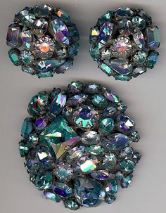 "Vintage unsigned Schreiner set has light blue and aqua faceted glass rhinestones. Some of the light blue ones have purple aurora borealis highlights. The first photo was taken with a scanner which brings them out. The pin measures 2-1/4"" and has a secure roll clasp closure. The clip-on earrings measure 1-5/16"" and weigh 24 grams for the pair. Overall very nice condition with some wear from age."
