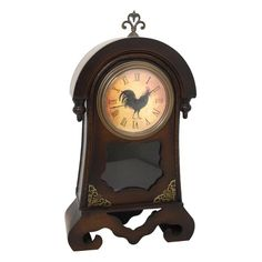 "This farm-inspired table clock features carved dark stained wood, and a small glass panel that accents the front of this clock, along with brass metal accents at the base of the clock. The face of the clock features individual roman numeral numbers and a rooster design in the center of the face of the clock. This clock is the perfect rustic accent to any space.  Overall Dimensions of This Table Clock: 18"" H x 10"" L x 3"" W  Batteries Not Included"