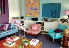 No projeto de Neza Cesar, o sofá e as almofadas puxam os tons das paredes: roxo e azul-claro. O tapete de listras dá sensação de amplitude ao ambiente