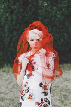 Image via Laura Hotz\\ As I look at this photo I am conflicted with innocence and sin. The veil, model, and floral dress suggests an innocent gesture. The veil however is tainted with red, a color of lust and revenge. Intersting.