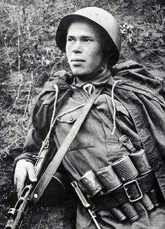 """On the Stalingrad Front, August, 1942: Recon scout N. Romanov poses with his PPSh-41 sub-machine gun and four hand grenades stuck in his belt. The one with the skirt is a ""pomegranate"" defensive grenade. Note also the scout knife."""