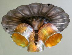 Antique Arts and Crafts flush mount light fixture with hammered metal and Quezal shades.