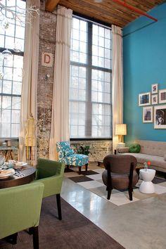 I want this room. High ceilings. Loft style. Brick wall. Chair. Sofa.