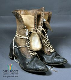 A pair of ladies', leather, high-topped boots with a plain heel and pointed toes. They are black toe to heel with brown tops and light coloured cotton laces. The boots are lined in white. Grey Roots Museum & Archives Collection.
