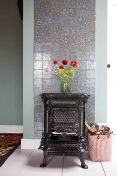 Deze houtkachel geeft een nostalgische sfeer in huis. Prachtig tegen een muurtje met gekleurde tegeltjes.