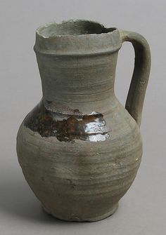 Jug, Date: ca. 1175–1250 Geography: Made in, Siegburg, Lower Rhineland, Germany Culture: German Medium: Earthenware, unglazed and partially salt glazed Dimensions: Overall: 7 3/4 x 5 9/16 x 5 1/16 in. (19.7 x 14.2 x 12.9 cm) Classification: Ceramics  Metropolitan Museum of Art  Accession Number: 1995.325