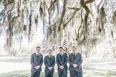 SAVANNAH WEDDINGS Groomsmen in grey suits  at Bethesda Academy's Whitfield Chapel with Spanish moss and oak trees by Mackensey Alexander
