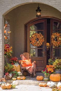 Park Hill Collection wreaths, a Maloca Baby Alpaca throw, and a Melissa Bamber Home cushion keep company with pumpkins on a porch dressed for fall. From: Victoria Magazine (FB) Park Hill Collection, Victoria Magazine, Autumn Garden, Porch Decorating, Decorating Ideas, Decor Ideas, Holiday Decorating, Craft Ideas, Fall Home Decor