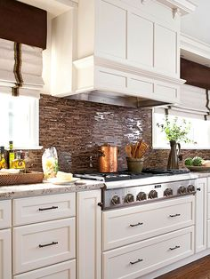 The veining in granite inspired the rich brown accents in this creamy-white kitchen. Shimmering shades of cocoa, chocolate, and coffee-color tiles cover the kitchen backsplash and coordinate with the oil-rubbed bronze cabinet hardware to create a luxurious traditional kitchen.