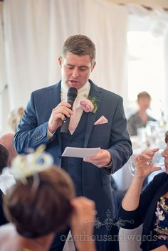 Toastmaster in blue suit with pink button hole and handkerchief . Photography by one thousand words wedding photographers