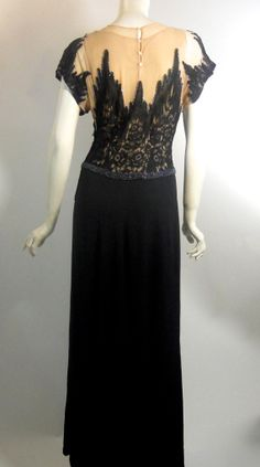 Devastating Black Illusion Lace Bodice Evening Gown circa 1940s Smashing 1940s gown of black crepe rayon with a sheer nude bodice layered in black cubist rose design lace. Side zip, 2 layers of nude nylon, back of neck buttons. Beaded waistline.