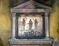 Household shrine from the House of Vettii in Pompeii. In the tympanum are the symbols of a sacrifice: a patera at the center, with a knife on the right and animal's skull on the left. Painted figures of Lares holding drinking horns and wine buckets flank the Genius of the family who is holding an incense box in his left hand. A serpent moves toward offerings on a small altar. The serpent, a common motif on these shrines, probably represents fertility, and thus the prosperity of the…