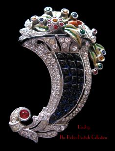 DuJay Invisibly Set Cornucopia.Exquisite and rare DuJay invisibly set faux sapphire cornucopia brooch with jeweled flowers and enamel leaves. Rhodium plated metal. The Robin Deutsch Collection