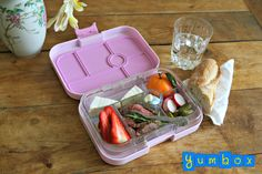 "French school lunch ""fait mason"". This Yumbox lunch has slices of herb rubbed beef roast over arugula, pickles, radishes, brie cheese, strawerribes, clementine, sugared almonds and a piece of crusty baguette on a side."