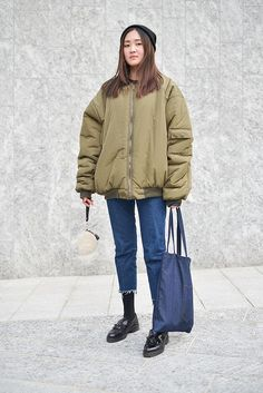 Street Style from Mens Fashion Week Fall 2016 - oversized olive green bomber jacket and frayed denim–casual outfit perfection.
