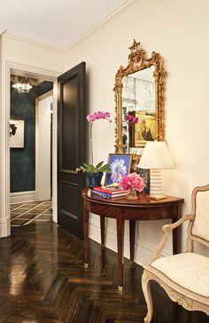 dark stained herringbone floors / demilune table / gold carved mirror/ black doors