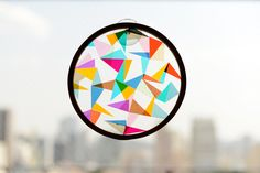 DIY suncatcher // page is in Portuguese but google translate gives the basic gist of gluing colored cellophane shapes onto plastic wrap sandwiched in an embroidery hoop
