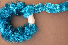 How have I never thought to make a wreath with tinsel??? Add snowflake ornaments