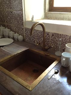poor iphone shot of one of my favorite kitchens... villa in tuscany. purple tile and concrete and brass.