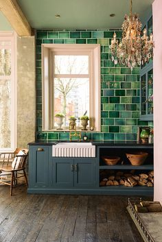 Hello beautiful glamorous colorful kitchen. Love those old wood floors, that gorgeous chandelier, that green tile against the millenial pink wall.