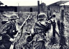 "Waffen SS during firefight at undetermined location on the Eastern Front. Note the man on the right deploying a Mauser C96 ""Broomhandle"" with stock. An unlikely weapon for a front line unit in WW2, the C96 in 7.63X25mm was extensively used during WW1. Its shoulder stock, long barrel, and high-velocity cartridge, had superior range and better penetration than most other pistols."