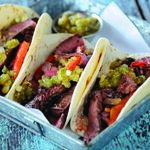 The charred tomatillo-green tomato sauce adds a pop of flavor to these skirt steak tacos. The recipe is from