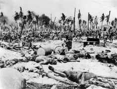 """""""INP Soundphoto. Some of 8,000 Japs who died on Kwajalein – Namur Island, Kwajalein Atoll…. Dramatic picture made after the fighting had ceased on Namur Island, showing hundreds of dead Japs littering the sandy ground near their blasted pillbox, while US Marines move up to the firing line in the background. 2-2-1944"""