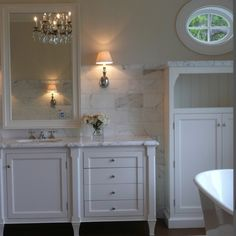 Stunning master bathroom with cream walls and window shaped like porthole.