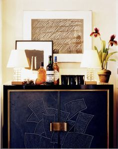 Cy Twombly art is the focal point and complement to this lovely contemporary sideboard. By keeping the height of the task lights low, the art & flowers are showcased.