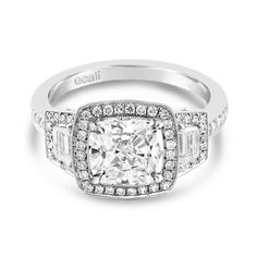 Ecali Presents: A magnificent 2ct square cushion centre stone is showcased within a milled bead halo with a pair of tapered baguettes and diamond band as the finishing touches on this white gold engagement ring.