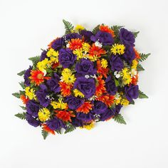 Mixed purple rose headstone spray with orange and yellow daisies.