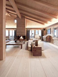Chalet moderne épuré, parquet, murs et plafond clairs, cheminée centrale, grand canapé